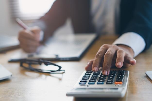 Bouchent la vue des mains de calculatrice utilisation homme d'affaires calculer financière des affaires. Photo Premium