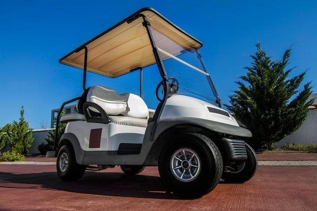 Bouchent la vue d'une voiturette de golf blanche garée sur la route. Photo Premium