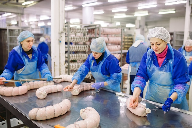 Bouchers Transformant Des Saucisses à Une Usine De Viande. Photo Premium