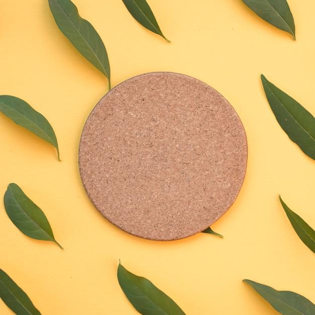 Bouchon circulaire blanc entouré de feuilles vertes sur fond jaune Photo gratuit