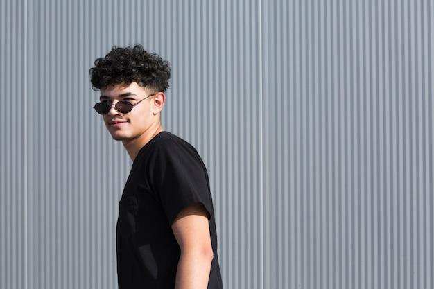Bouclé, homme, lunettes soleil, regarder, loin, gris, barrière Photo gratuit