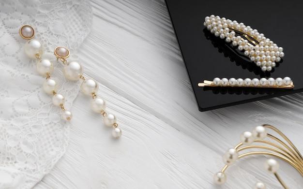 Boucles d'oreilles, bracelet et épingles à cheveux en or et perles sur une surface en bois Photo Premium