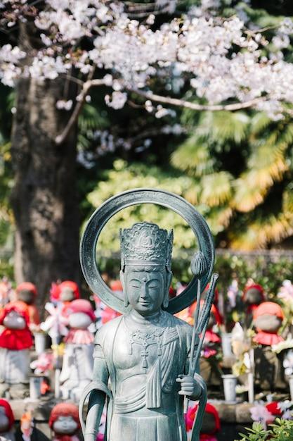 Bouddha et sakura dans le temple du japon Photo gratuit