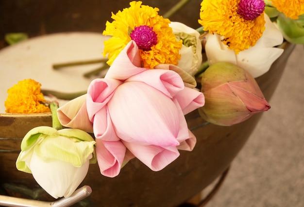 Bouddhiste mettant des lotus et des fleurs de souci à bouddha Photo Premium