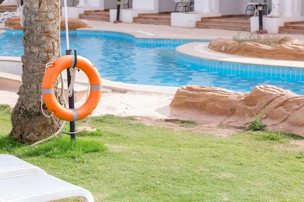 Bouée de sauvetage sur la clôture, au bord de la piscine en vacances à l'hôtel Photo Premium