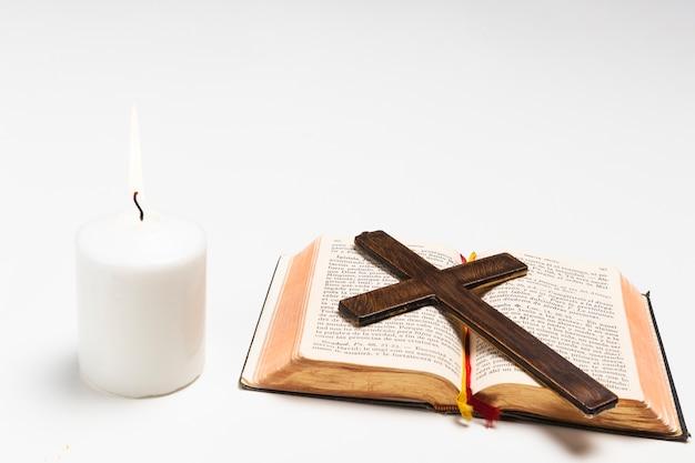 Bougie allumée avec livre sacré et croix Photo gratuit
