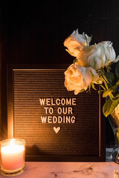 Bougie allumée et roses près du cadre noir avec bienvenue à notre message de mariage Photo gratuit