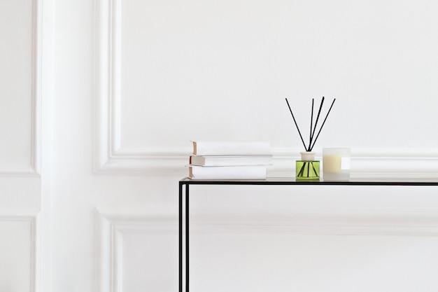 Bougie et assainisseur aromatique de roseaux sur la table dans le salon spa. arôme liquide dans une bouteille en verre avec des bâtons de roseau. diffuseur d'arômes de luxe dans la chambre. hygge. bougies scandinaves, parfum, livres Photo Premium
