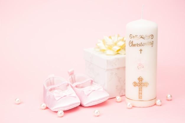 a4a3d16196248 Bougie de baptême avec des chaussons de bébé rose et boîte-cadeau Photo  Premium