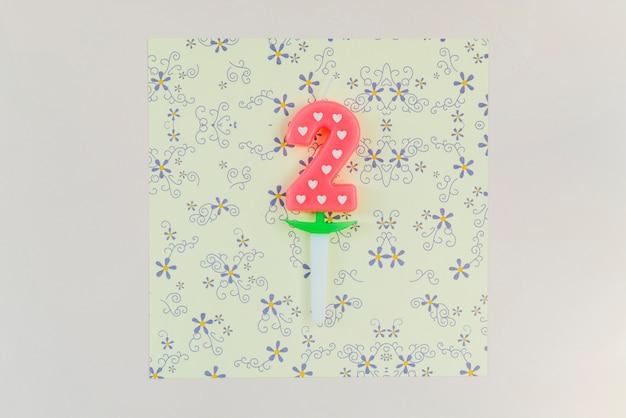 Bougie de deux ans sur papier floral artisanal sur le fond coloré Photo gratuit