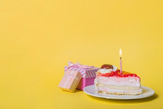 Bougie éclairée sur une tranche de gâteau avec deux boîtes-cadeaux sur fond jaune Photo gratuit