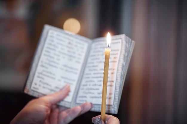 Bougie à la main et un livre de prières en gros plan dans l'église orthodoxe Photo Premium
