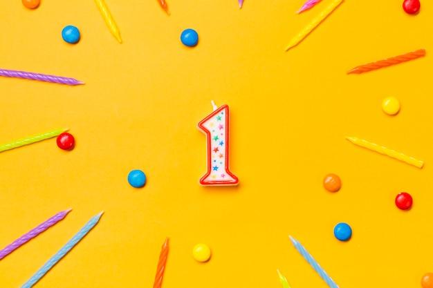 Bougie numéro un rouge entourée de bougies colorées et de gemmes sur fond jaune Photo gratuit