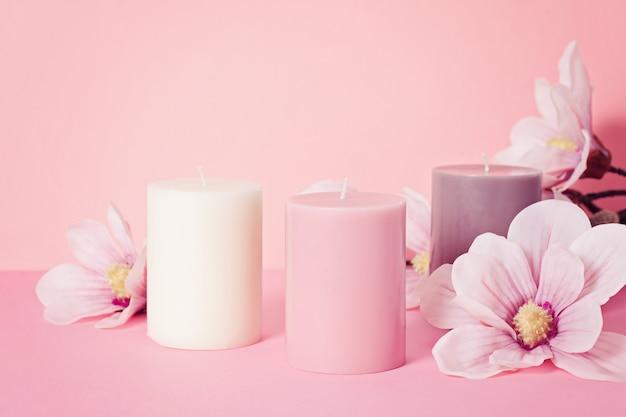 Bougie parfumée délicate fleur sur fond rose pastel Photo Premium