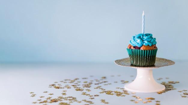 Bougie sur petit gâteau sur le cakestand sur fond bleu Photo gratuit