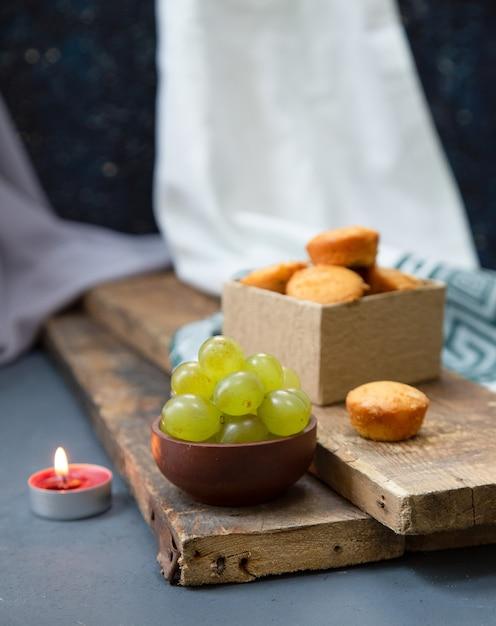 Bougie rouge, une boîte de muffins et raisins verts sur un morceau de bois Photo gratuit