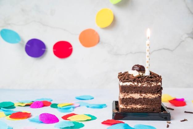 Bougie sur la tranche de gâteau et confettis sur table Photo gratuit