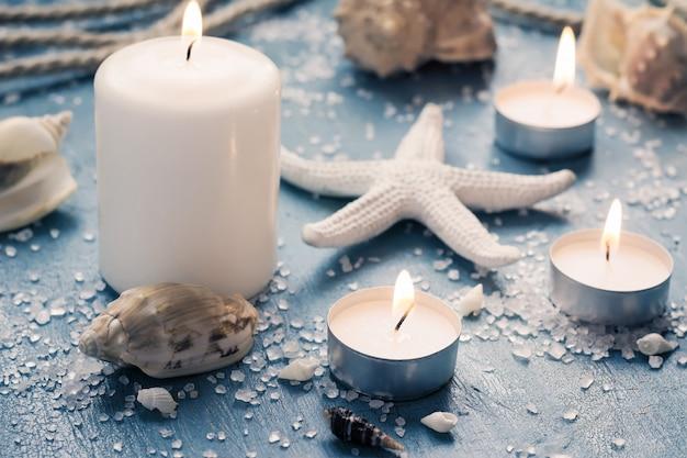 Des bougies allumées sur des objets de la marine, monochromes dans les tons bleu et blanc Photo Premium