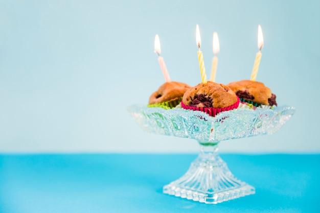 Bougies allumées sur le petit gâteau sur fond bleu Photo gratuit