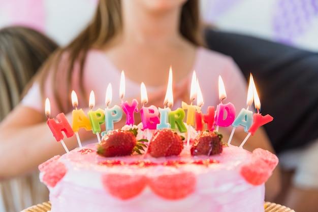 Bougies d'anniversaire rougeoyantes multicolores sur un gâteau à la fraise Photo gratuit