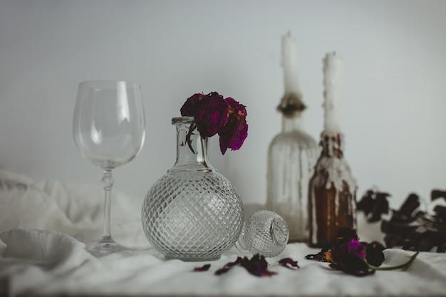 Bougies Sur Les Bouteilles à Côté D'un Vase Avec Une Fleur à L'intérieur Et Un Verre Photo gratuit