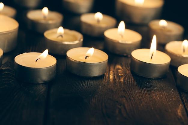 Des bougies brûlent dans l'obscurité sur le noir. concept de commémoration. Photo Premium