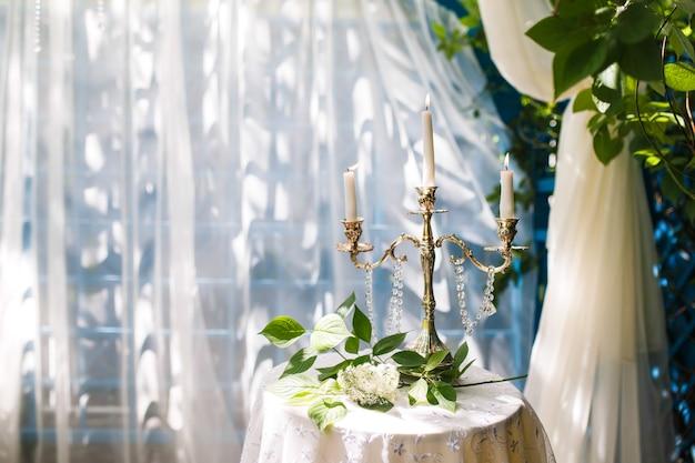 Bougies en chandeliers sur la table. une branche d'arbre se trouve ensuite. décoration de mariage. Photo Premium