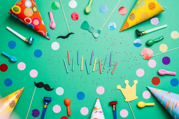 Bougies colorées entourées de chapeaux de fête; des ballons; accessoires d'anniversaire et confettis sur fond vert Photo gratuit