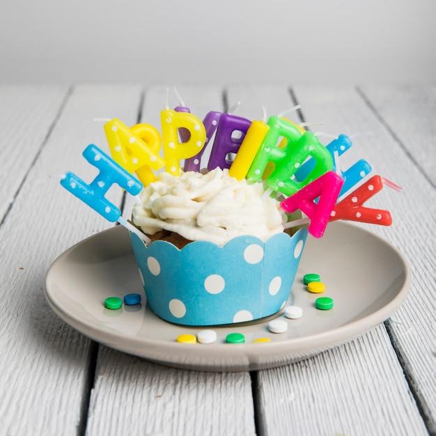 Bougies colorées de joyeux anniversaire insérées dans un seul petit gâteau sur une plaque sur la table en bois Photo gratuit