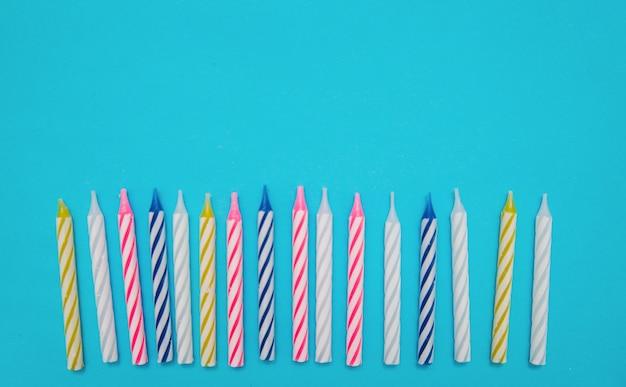 Des Bougies Colorées Sont Placées Dans Une Rangée Pour Un Gâteau D'anniversaire Sur Fond Bleu Photo Premium