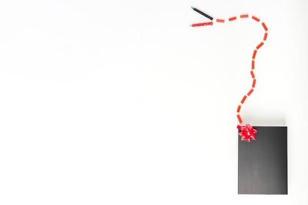 Bougies connectées avec des bonbons au coffret noir avec un arc décoratif rouge sur fond blanc Photo gratuit