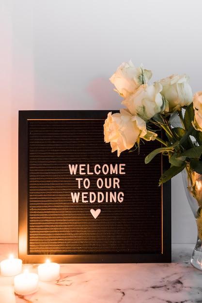 Des bougies lumineuses près du mariage accueillent un cadre noir et un vase sur fond blanc Photo gratuit