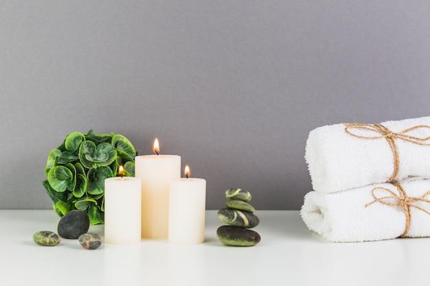 Bougies lumineuses; serviette et pierres de spa sur une table blanche Photo gratuit