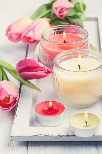 Bougies parfumées jaunes et roses avec des tulipes Photo Premium