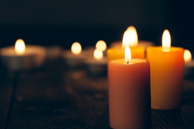 Bougies qui brûlent dans l'obscurité sur fond noir Photo Premium