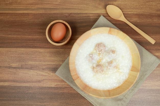 Bouillie De Riz Avec Boulette De Viande, Oeuf Et Cuillère Sur Une Table En Bois Photo Premium