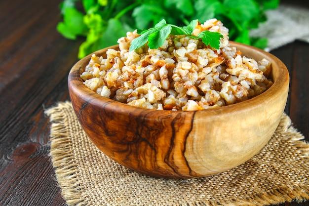 Bouillie de sarrasin dans un bol avec des morceaux de viande de poulet et de coriandre sur une table en bois brune. Photo Premium
