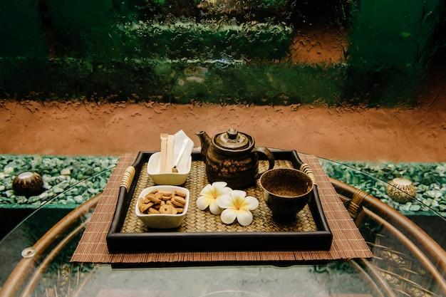 Bouilloire à thé en bronze antique en bronze sur un plateau en osier avec des fleurs de lotus Photo Premium