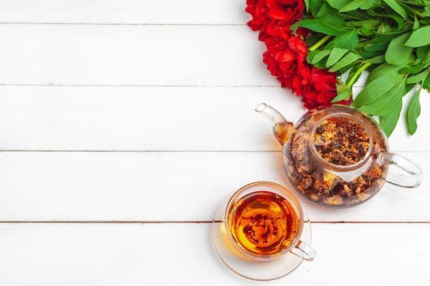 Bouilloire en verre de tisane avec des fleurs fraîches se bouchent Photo Premium