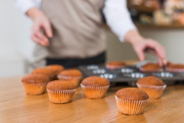 Boulanger femme floue enlever les muffins du plateau sur la table en bois texturé Photo gratuit