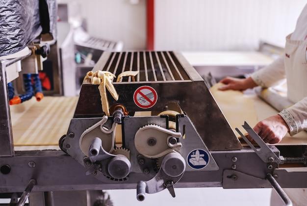Boulanger Travailleur En Uniforme Blanc Faisant Des Croûtes à Tarte Sur La Machine En Boulangerie. Photo Premium