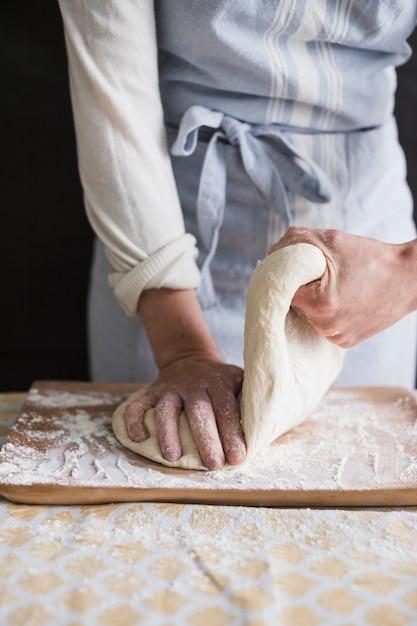 Une boulangère, pétrir la pâte avec de la farine sur une planche à découper Photo gratuit