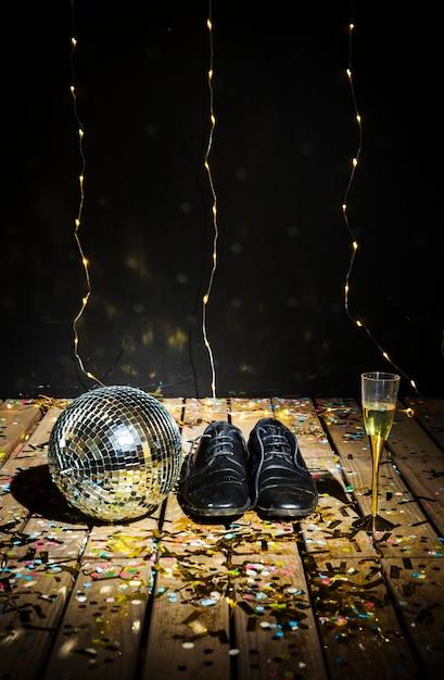 Boule disco, bottes d'homme et verre de boisson entre des confettis Photo gratuit
