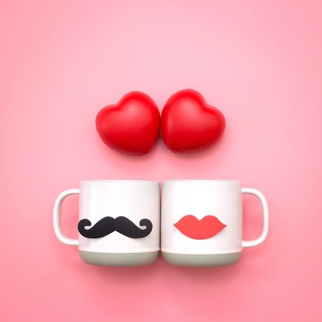 Boule en forme de coeur et papier faux décor de lèvres et moustaches sur une tasse rose sur fond rose. Photo Premium