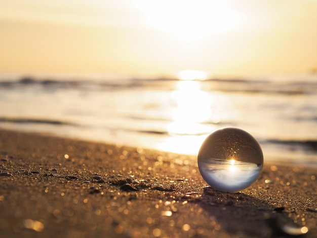Boule de lentille avec reflet doré sunrise à la plage d'été. Photo Premium