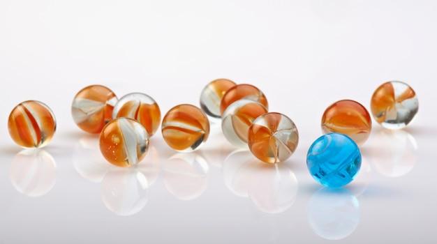 Une boule de marbre bleue se démarquer de la foule sur blanc Photo Premium
