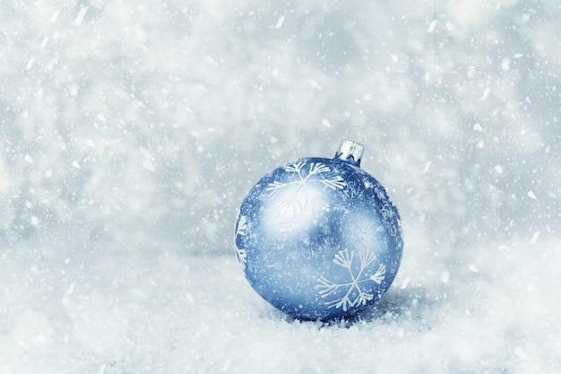 Boule de noël bleue sur la neige Photo Premium