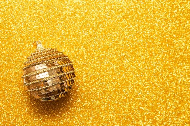 Boule de noël décorative sur fond de paillettes dorées Photo Premium