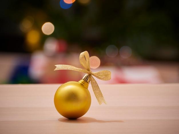 Boule De Noël Noeud De Ruban D'or Avec Arbre De Noël Décoré Flou Et Lumières Bokeh En Arrière-plan. Espace Pour Le Texte Photo Premium