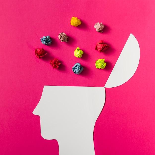 Boule de papier froissé coloré au-dessus de la tête humaine blanche découpée sur fond rose Photo gratuit